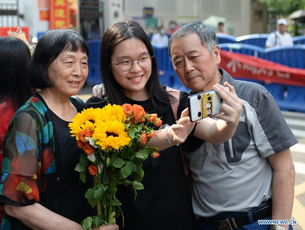 An examinee poses for photo with families outside an exam site at a middle school in Changsha, capital of central China's Hunan Province, June 9, 2021. China's annual college entrance exam concluded on Tuesday in some parts of the country. (Xinhua/Chen Zhenhai)