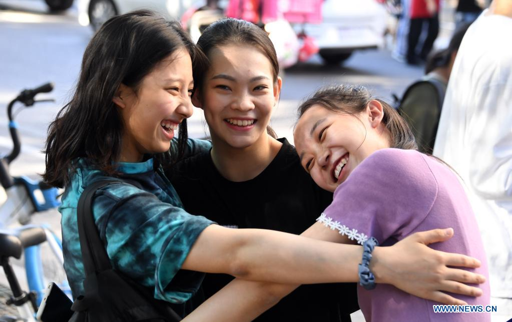 Examinees hug each other outside an exam site at a middle school in Beijing, capital of China, June 10, 2021. The annual college entrance exam concluded Thursday in Beijing. (Xinhua/Ren Chao)