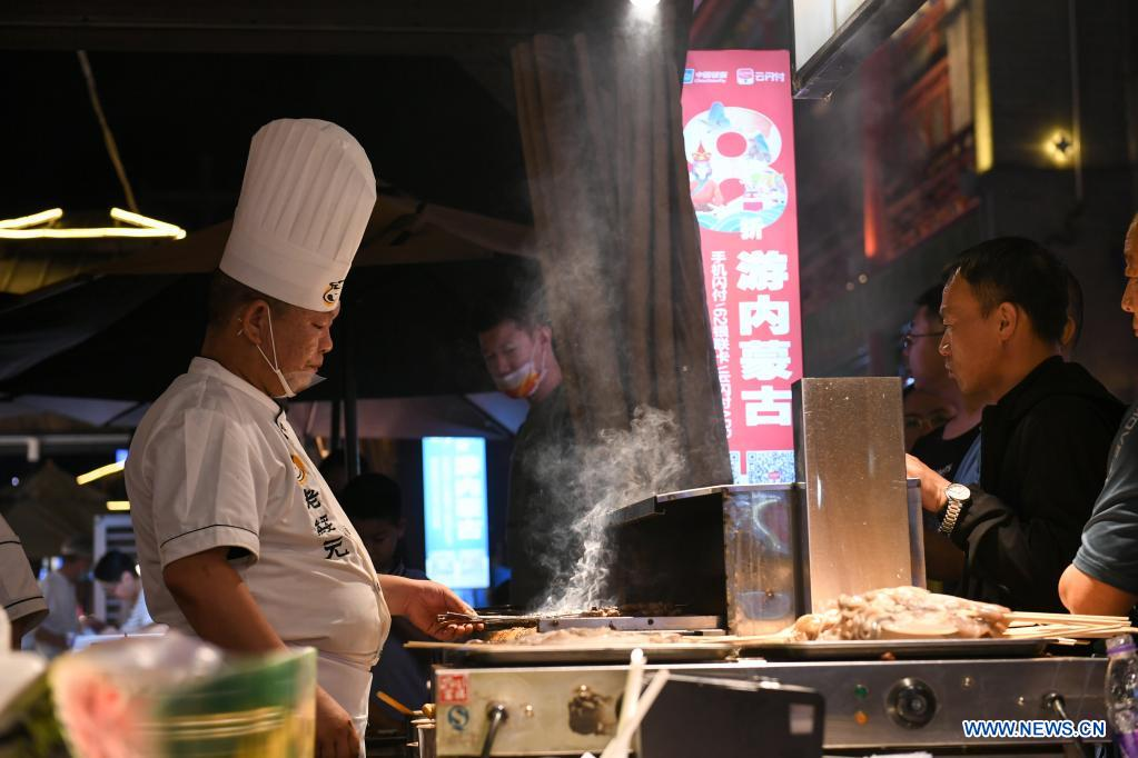 A cook grills lamb skewers in Hohhot, north China's Inner Mongolia Autonomous Region, June 10, 2021. Various activities such as appreciating traditional music and tasting local food are held here to promote tourism. (Xinhua/Bei He)