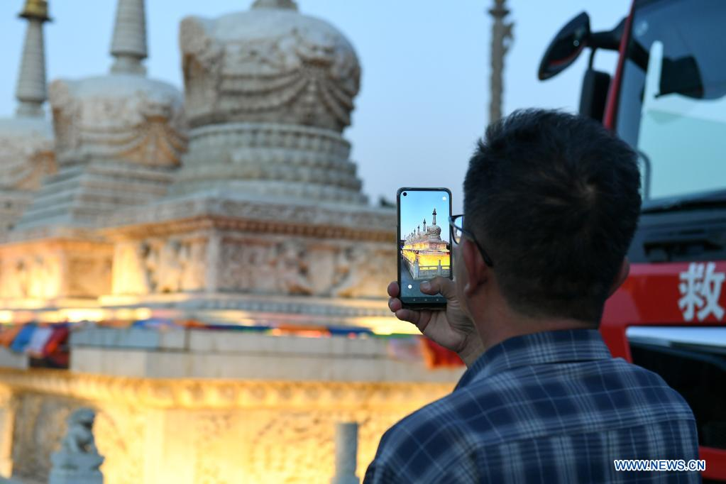 A tourist takes a photo while sightseeing in Hohhot, north China's Inner Mongolia Autonomous Region, June 10, 2021. Various activities such as appreciating traditional music and tasting local food are held here to promote tourism. (Xinhua/Bei He)