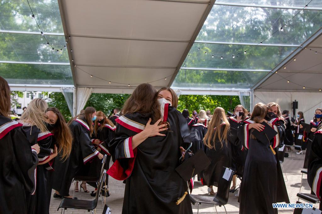 Students embrace each other during a graduation ceremony at Riga Stradins University in Riga, Latvia, on June 29, 2021. (Photo by Edijs Palens/Xinhua)