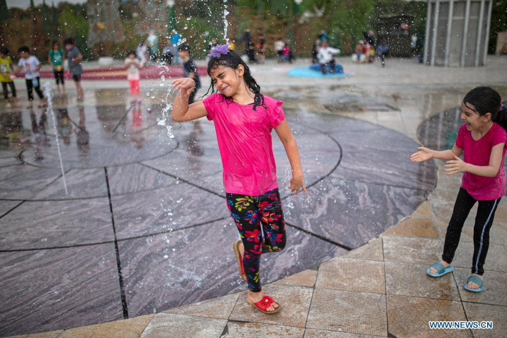 Children cool off at a splash pad during hot weather at a park in Tehran, Iran, on June 29, 2021. (Photo by Ahmad Halabisaz/Xinhua)