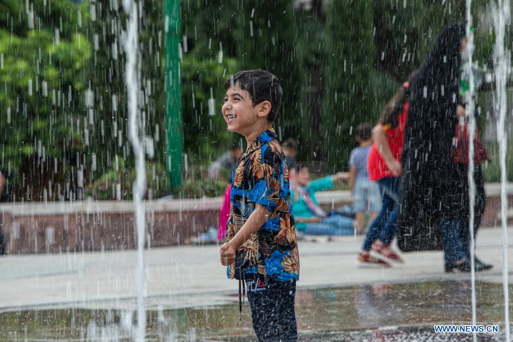A boy cools off at a splash pad during hot weather at a park in Tehran, Iran, on June 29, 2021. (Photo by Ahmad Halabisaz/Xinhua)