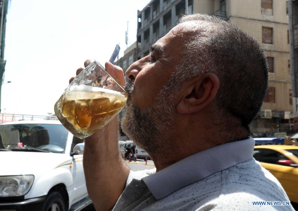 A man has a cold drink to cool off in Baghdad, Iraq, on June 29, 2021. Scorching weather started here in June and temperatures rose to about 50 degrees Celsius. (Photo by Omar Khalil/Xinhua)