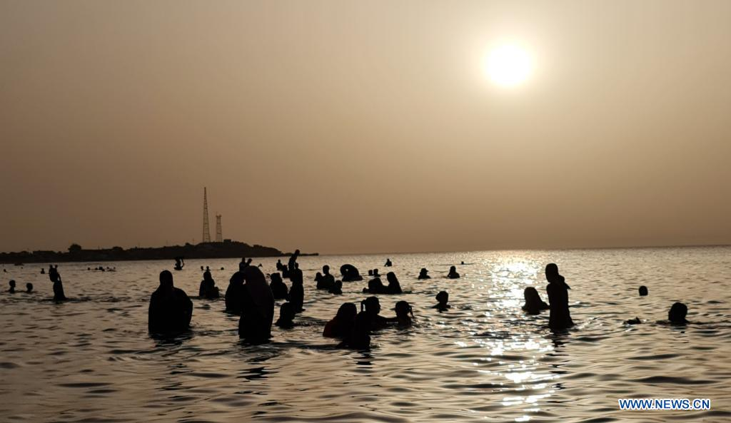 People cool off in the sea off Garrabulli town, some 55 km east of Tripoli, Libya, on June 29, 2021. The heat wave hit the western region of Libya with temperatures around 40 degrees Celsius. (Photo by Hamza Turkia/Xinhua)