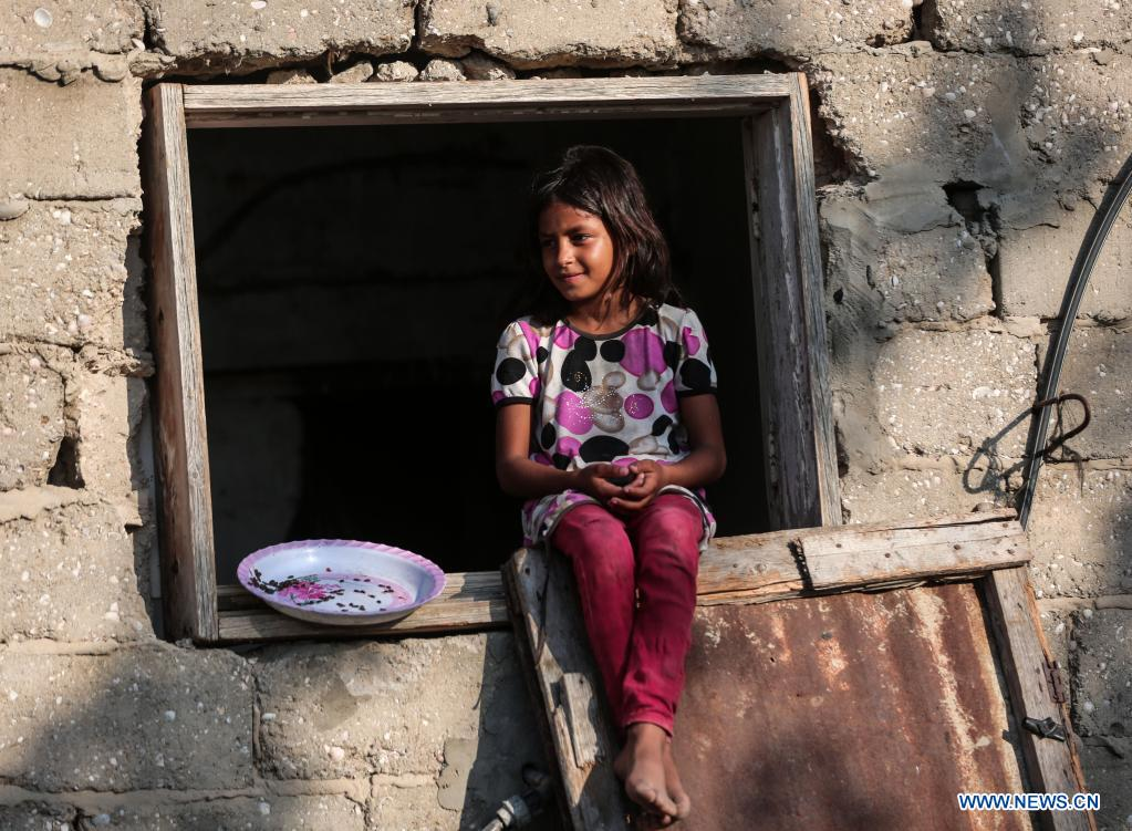 A Palestinian girl sits at the window of a house during hot weather near Khan Younis refugee camp in southern Gaza Strip, on June 29, 2021. (Photo by Yasser Qudih/Xinhua)