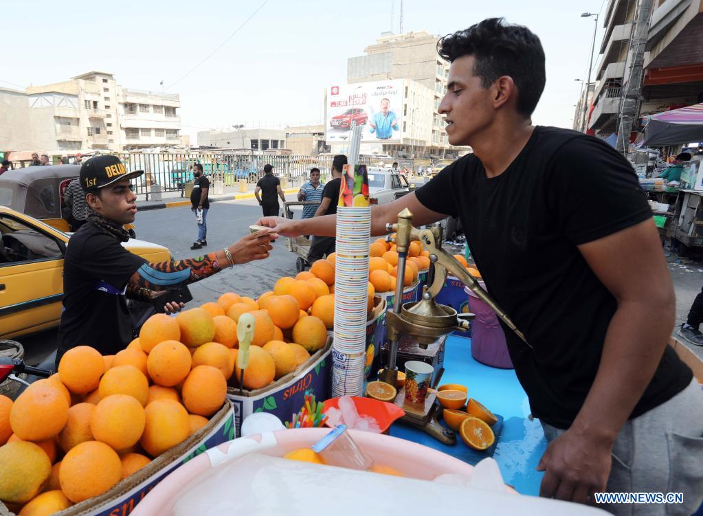 A seller hands a cup of juice to a customer in Baghdad, Iraq, on June 29, 2021. Scorching weather started here in June and temperatures rose to about 50 degrees Celsius. (Photo by Omar Khalil/Xinhua)