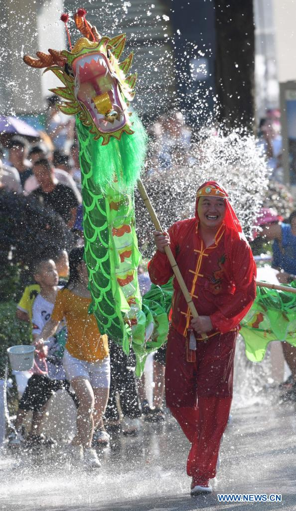 A dragon dance team performs amid splashes of water to celebrate