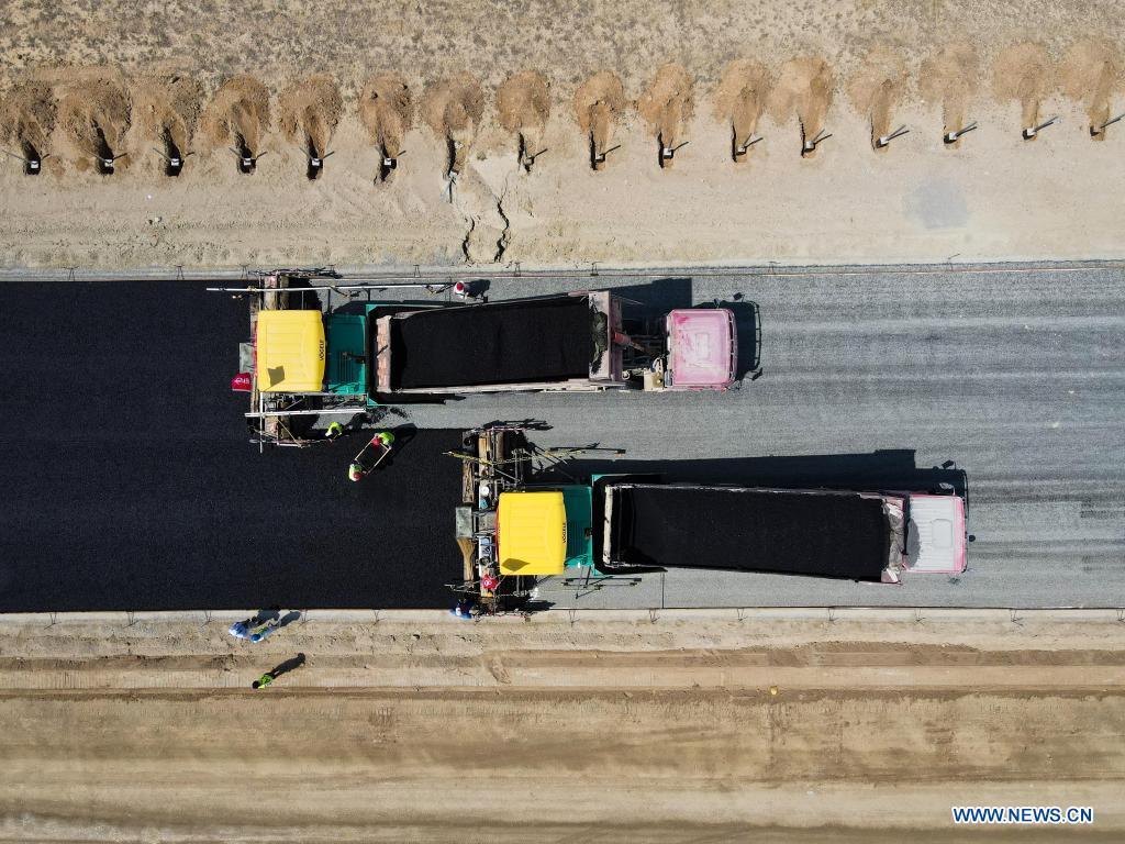 In this aerial photo, vehicles pave a section of a cross-desert expressway with asphalt in northwest China's Xinjiang Uygur Autonomous Region, July 16, 2021. Construction of the first cross-desert expressway in Xinjiang has proceeded smoothly. The expressway, linking Altay Prefecture and the regional capital city of Urumqi, stretches some 343 km, with sections of more than 150 km built through the desert. (Xinhua/Gao Han)