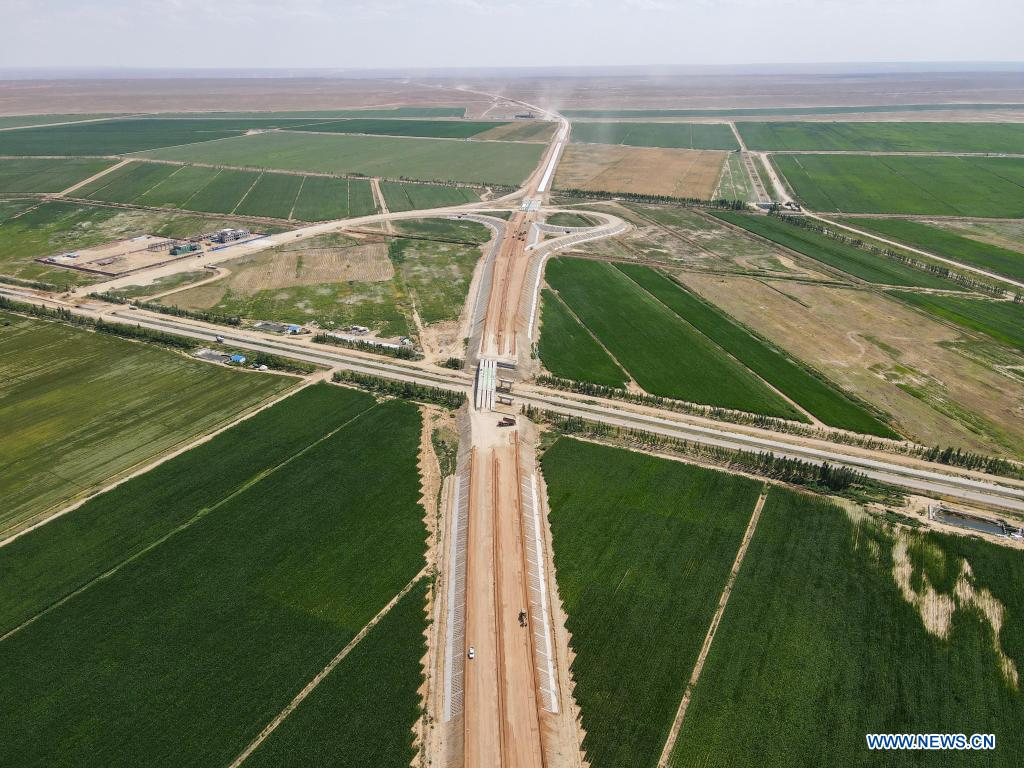 Aerial photo taken on July 16, 2021 shows a construction site of a cross-desert expressway in northwest China's Xinjiang Uygur Autonomous Region. Construction of the first cross-desert expressway in Xinjiang has proceeded smoothly. The expressway, linking Altay Prefecture and the regional capital city of Urumqi, stretches some 343 km, with sections of more than 150 km built through the desert. (Xinhua/Gao Han)