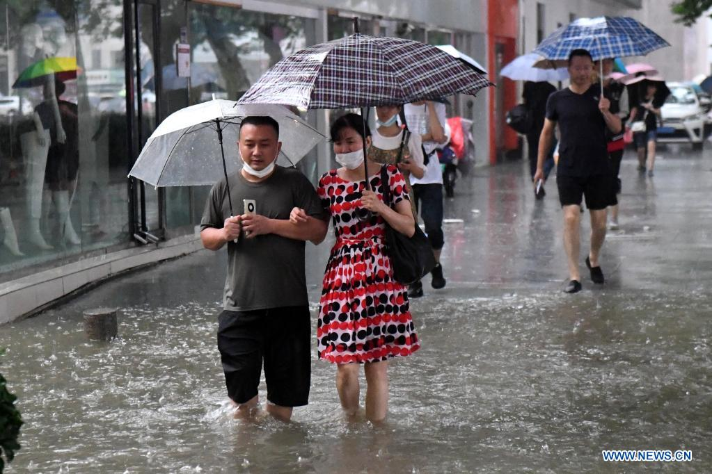 People wade through a waterlogged road in Zhengzhou, capital of central China's Henan Province, July 20, 2021. More than 144,660 residents have been affected by torrential rains in central China's Henan Province since July 16, and 10,152 have been relocated to safe places, the provincial flood control and drought relief headquarters said Tuesday. A total of 16 large and medium-sized reservoirs have seen water levels rise above the alert level after torrential rains battered most parts of the province on Monday and Tuesday. (Xinhua/Zhu Xiang)