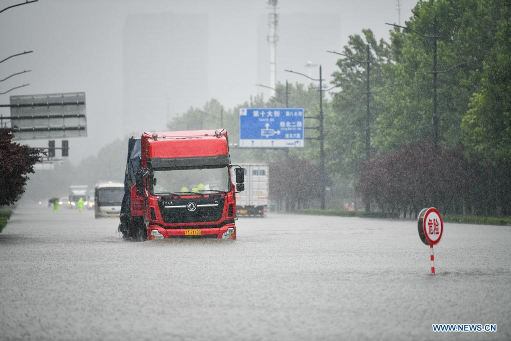 Vehicles run on a waterlogged road in Zhengzhou, capital of central China's Henan Province, July 20, 2021. More than 144,660 residents have been affected by torrential rains in central China's Henan Province since July 16, and 10,152 have been relocated to safe places, the provincial flood control and drought relief headquarters said Tuesday. A total of 16 large and medium-sized reservoirs have seen water levels rise above the alert level after torrential rains battered most parts of the province on Monday and Tuesday. (Photo by Hou Jianxun/Xinhua)