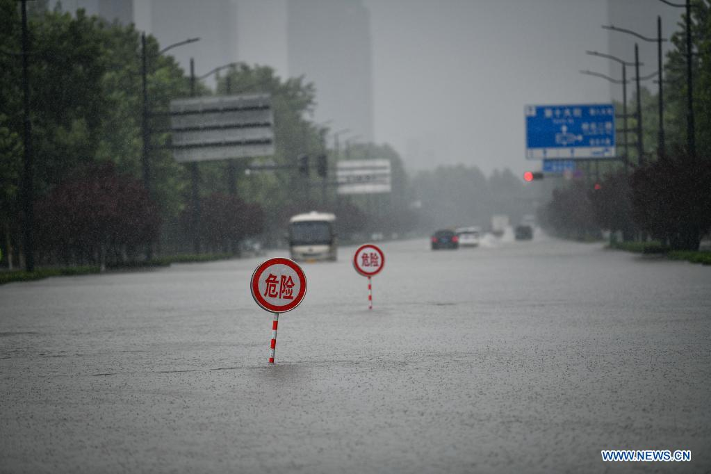 Danger signs are installed on a waterlogged road in Zhengzhou, capital of central China's Henan Province, July 20, 2021. More than 144,660 residents have been affected by torrential rains in central China's Henan Province since July 16, and 10,152 have been relocated to safe places, the provincial flood control and drought relief headquarters said Tuesday. A total of 16 large and medium-sized reservoirs have seen water levels rise above the alert level after torrential rains battered most parts of the province on Monday and Tuesday. (Photo by Hou Jianxun/Xinhua)