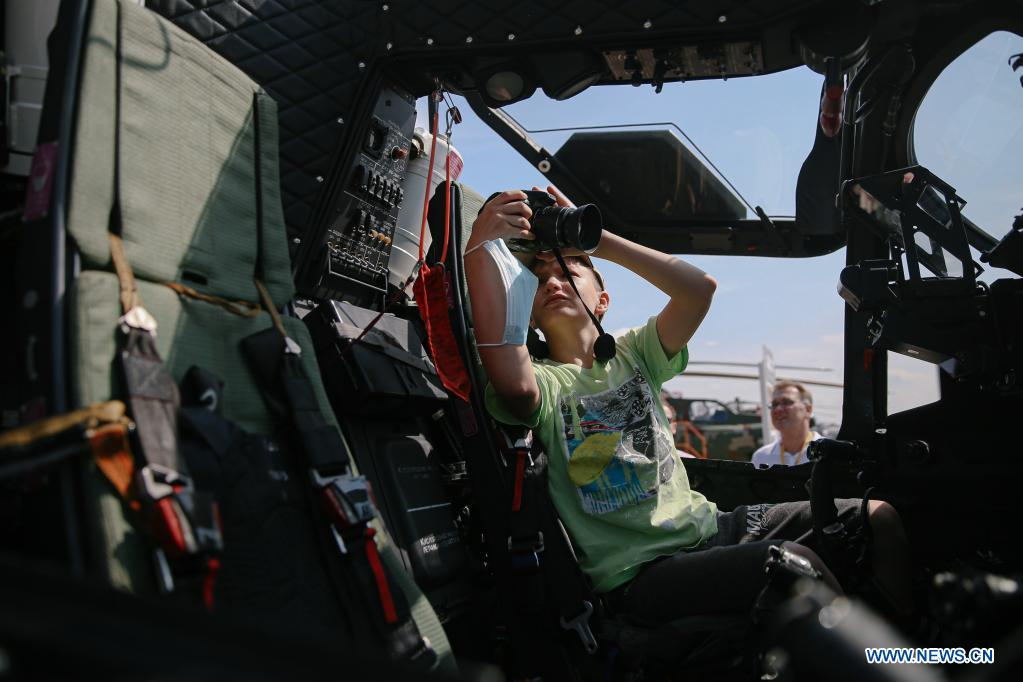 A boy takes a photo inside the cabin of a Mi-28NE helicopter during the opening day of the International Aviation and Space Salon (MAKS)-2021 in a Moscow suburb, Russia, on July 20, 2021. MAKS-2021 kicked off in a Moscow suburb on Tuesday. (Xinhua/Evgeny Sinitsyn)