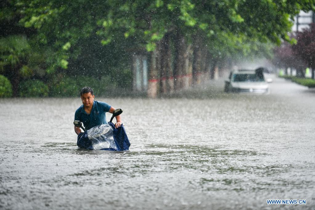 A man rides on a waterlogged road in Zhengzhou, capital of central China's Henan Province, July 20, 2021. More than 144,660 residents have been affected by torrential rains in central China's Henan Province since July 16, and 10,152 have been relocated to safe places, the provincial flood control and drought relief headquarters said Tuesday. A total of 16 large and medium-sized reservoirs have seen water levels rise above the alert level after torrential rains battered most parts of the province on Monday and Tuesday. (Photo by Hou Jianxun/Xinhua)