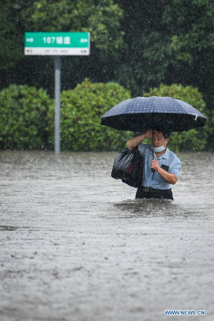 A man wades through a waterlogged road in Zhengzhou, capital of central China's Henan Province, July 20, 2021. More than 144,660 residents have been affected by torrential rains in central China's Henan Province since July 16, and 10,152 have been relocated to safe places, the provincial flood control and drought relief headquarters said Tuesday. A total of 16 large and medium-sized reservoirs have seen water levels rise above the alert level after torrential rains battered most parts of the province on Monday and Tuesday. (Photo by Hou Jianxun/Xinhua)