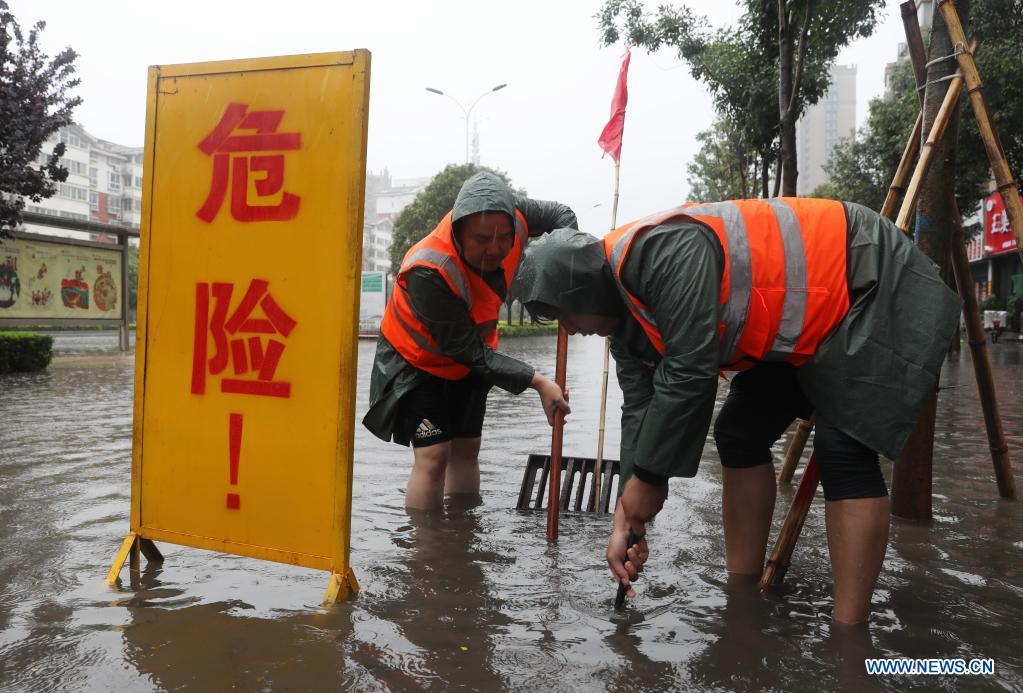 Staff members drain water at a waterlogged area in Wuzhi County, central China's Henan Province, July 20, 2021. Wuzhi County of Jiaozuo has recently witnessed continuous rainfalls. Flood-control measures such as water draining, patrolling embankments and traffic control were carried out to protect the safety of people's lives and property. (Photo by Feng Xiaomin/Xinhua)