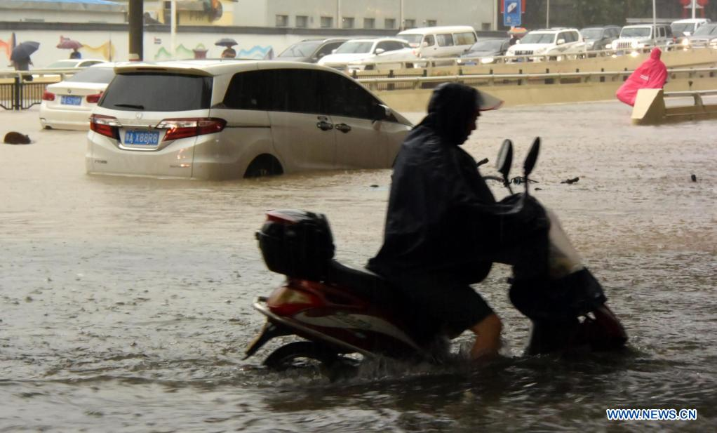 A man rides on a waterlogged road in Zhengzhou, capital of central China's Henan Province, July 20, 2021. More than 144,660 residents have been affected by torrential rains in central China's Henan Province since July 16, and 10,152 have been relocated to safe places, the provincial flood control and drought relief headquarters said Tuesday. A total of 16 large and medium-sized reservoirs have seen water levels rise above the alert level after torrential rains battered most parts of the province on Monday and Tuesday. (Xinhua/Zhu Xiang)