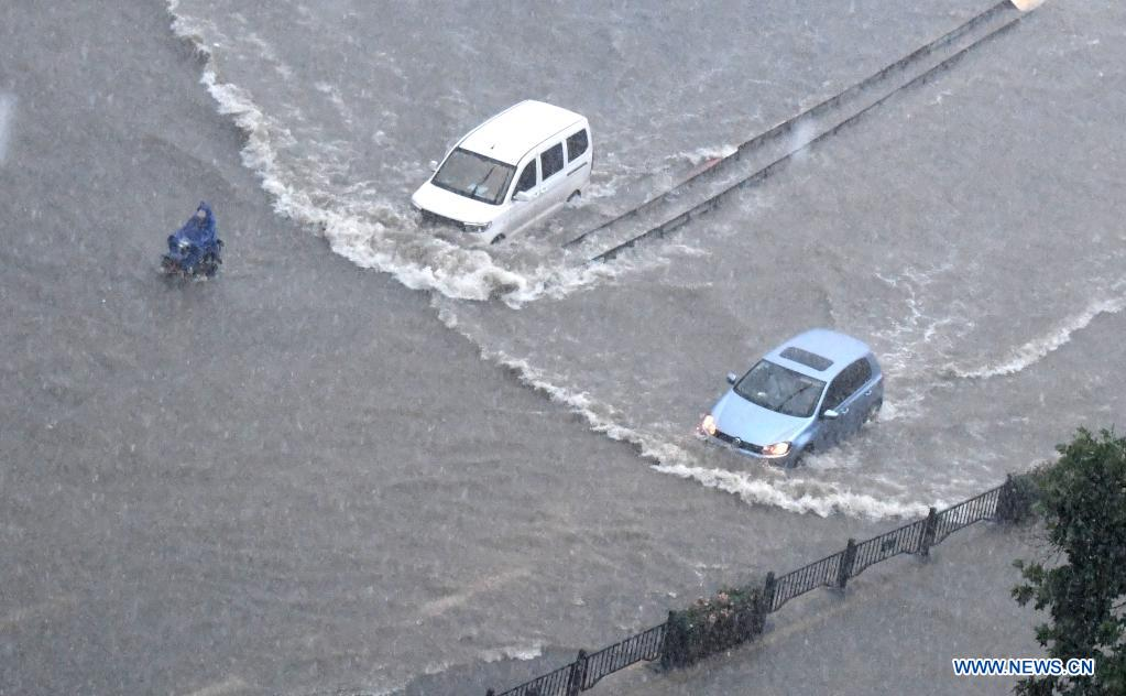 Vehicles run on a waterlogged road in Zhengzhou, capital of central China's Henan Province, July 20, 2021. More than 144,660 residents have been affected by torrential rains in central China's Henan Province since July 16, and 10,152 have been relocated to safe places, the provincial flood control and drought relief headquarters said Tuesday. A total of 16 large and medium-sized reservoirs have seen water levels rise above the alert level after torrential rains battered most parts of the province on Monday and Tuesday. (Xinhua/Zhu Xiang)
