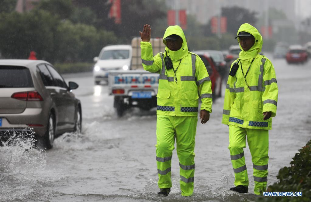 Policemen direct traffic at a waterlogged area in Wuzhi County, central China's Henan Province, July 20, 2021. Wuzhi County of Jiaozuo has recently witnessed continuous rainfalls. Flood-control measures such as water draining, patrolling embankments and traffic control were carried out to protect the safety of people's lives and property. (Photo by Feng Xiaomin/Xinhua)
