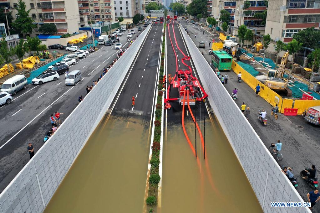 In this aerial photo, firefighters pump rainwater out of a road in Zhengzhou, capital of central China's Henan Province, July 21, 2021. Extremely heavy rainfall hit Henan on Tuesday, with precipitation in Zhengzhou, exceeding the highest level on local weather records. A rescue team of 1,800 firefighters has been deployed to the flood-hit region from seven neighboring provinces, together with boats, pumping vehicles, and flood rescue kits. (Photo by Ma Xiaoran/Xinhua)