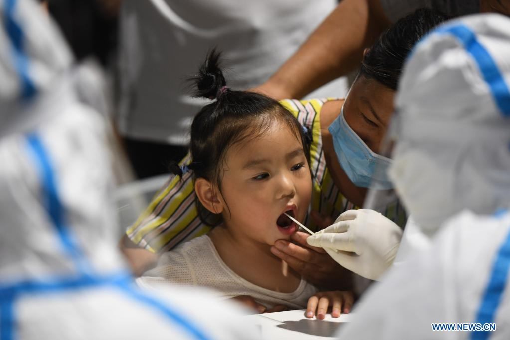 A medical worker takes a swab sample from a girl for COVID-19 test at a testing site in Nanjing, east China's Jiangsu Province, July 21, 2021. Nanjing, which has a population of more than 9.3 million, carried out citywide nucleic acid testing starting on Wednesday. (Xinhua/Ji Chunpeng)