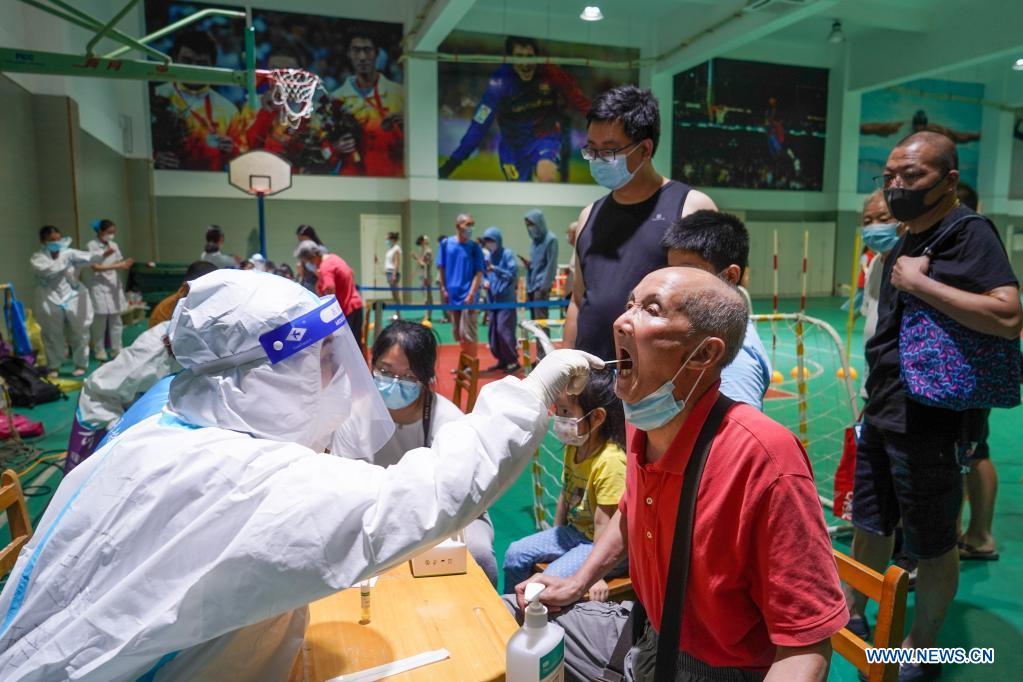 A medical worker takes a swab sample from an elderly man for COVID-19 test at a testing site in Nanjing, east China's Jiangsu Province, July 21, 2021. Nanjing, which has a population of more than 9.3 million, carried out citywide nucleic acid testing starting on Wednesday. (Xinhua/Li Bo)