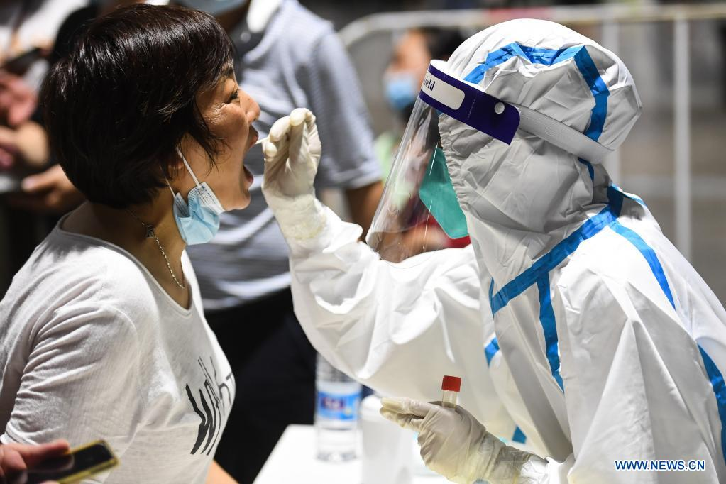A medical worker takes a swab sample from a woman for COVID-19 test at a testing site in Nanjing, east China's Jiangsu Province, July 21, 2021. Nanjing, which has a population of more than 9.3 million, carried out citywide nucleic acid testing starting on Wednesday. (Xinhua/Ji Chunpeng)