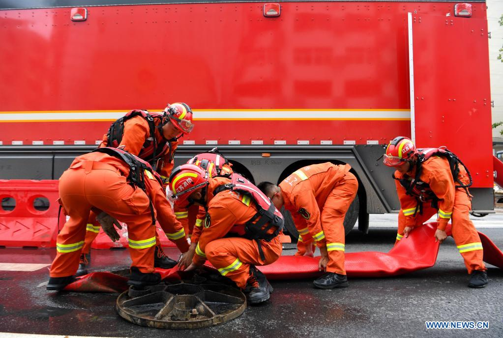 Firefighters put the drainage pipe in place in Zhengzhou, capital of central China's Henan Province, July 21, 2021. Extremely heavy rainfall hit Henan on Tuesday, with precipitation in Zhengzhou, exceeding the highest level on local weather records. A rescue team of 1,800 firefighters has been deployed to the flood-hit region from seven neighboring provinces, together with boats, pumping vehicles, and flood rescue kits. (Xinhua/Hao Yuan)