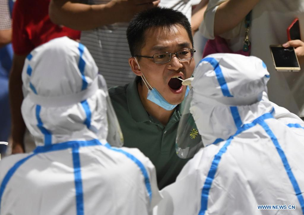 A medical worker takes a swab sample from a man for COVID-19 test at a testing site in Nanjing, east China's Jiangsu Province, July 21, 2021. Nanjing, which has a population of more than 9.3 million, carried out citywide nucleic acid testing starting on Wednesday. (Xinhua/Ji Chunpeng)