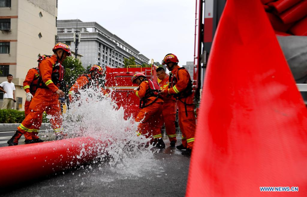 Firefighters pump rainwater out of a road in Zhengzhou, capital of central China's Henan Province, July 21, 2021. Extremely heavy rainfall hit Henan on Tuesday, with precipitation in Zhengzhou, exceeding the highest level on local weather records. A rescue team of 1,800 firefighters has been deployed to the flood-hit region from seven neighboring provinces, together with boats, pumping vehicles, and flood rescue kits. (Xinhua/Hao Yuan)