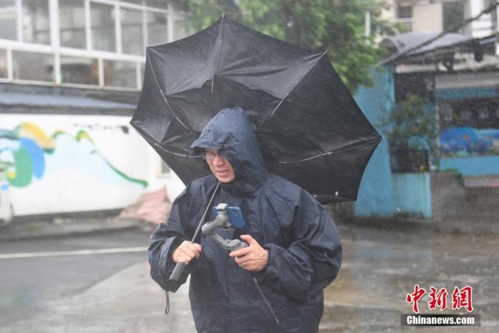 7月26日,浙江嘉兴,一名媒体记者的雨伞被吹翻。 中新社记者 王刚 摄
