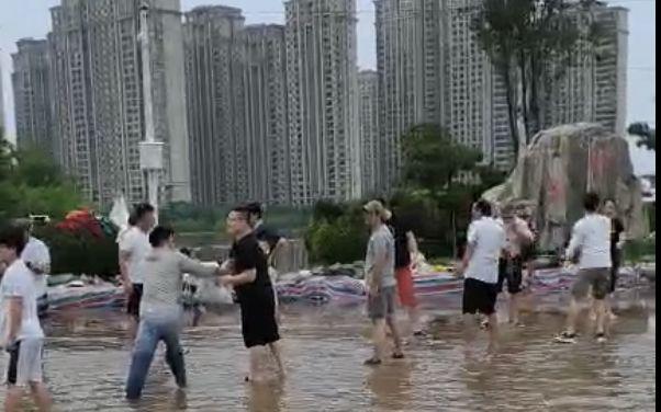 23日,志愿者们在水中传递沙袋、物资。受访者供图