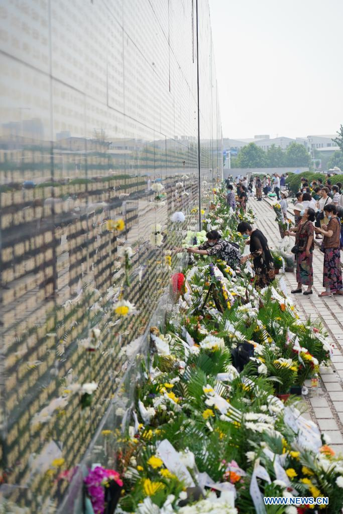 People present flowers in front of a memorial wall at the Tangshan Earthquake Memorial Park in Tangshan, north China's Hebei Province, July 28, 2021. Wednesday marks the 45th anniversary of the Tangshan earthquake. The 7.8-magnitude quake struck the city of Tangshan in Hebei Province on July 28, 1976, killing more than 240,000 people and destroying virtually all buildings. (Xinhua/Mu Yu)