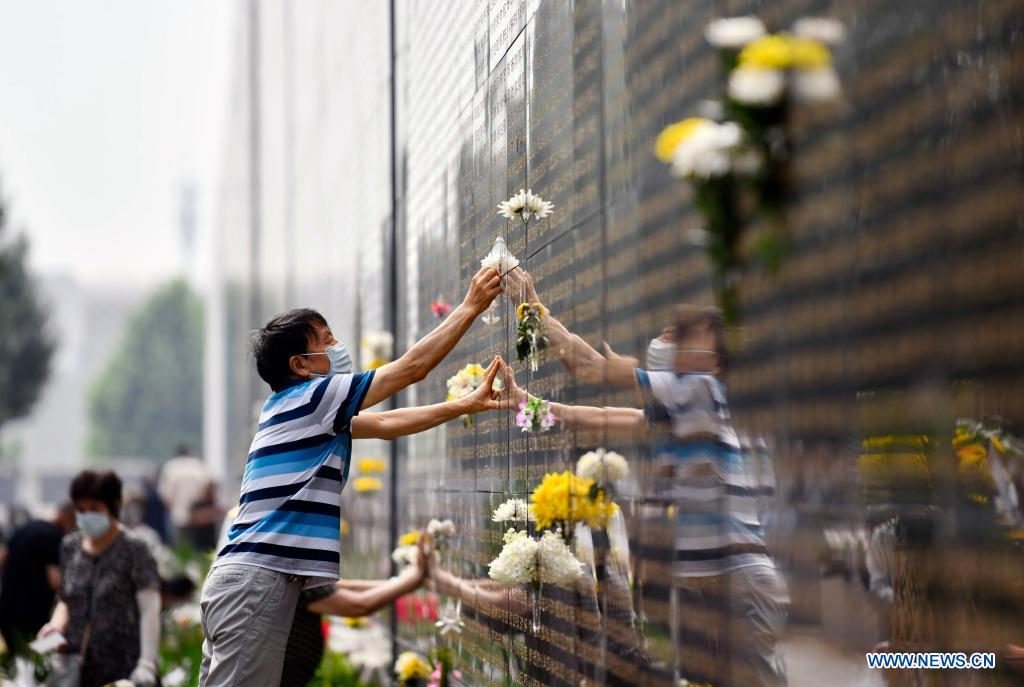 A resident presents flowers in front of a memorial wall at the Tangshan Earthquake Memorial Park in Tangshan, north China's Hebei Province, July 28, 2021. Wednesday marks the 45th anniversary of the Tangshan earthquake. The 7.8-magnitude quake struck the city of Tangshan in Hebei Province on July 28, 1976, killing more than 240,000 people and destroying virtually all buildings. (Photo by Zhao Liang/Xinhua)