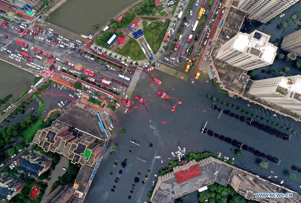 Aerial photo taken on July 28, 2021 shows rescuers pumping rainwater out of a road in flood-hit Weihui City, central China's Henan Province. Weihui City suffered from severe urban waterlogging due to the extremely heavy rainfall. Rescue and drainage work is still in progress there. (Xinhua/Li An)