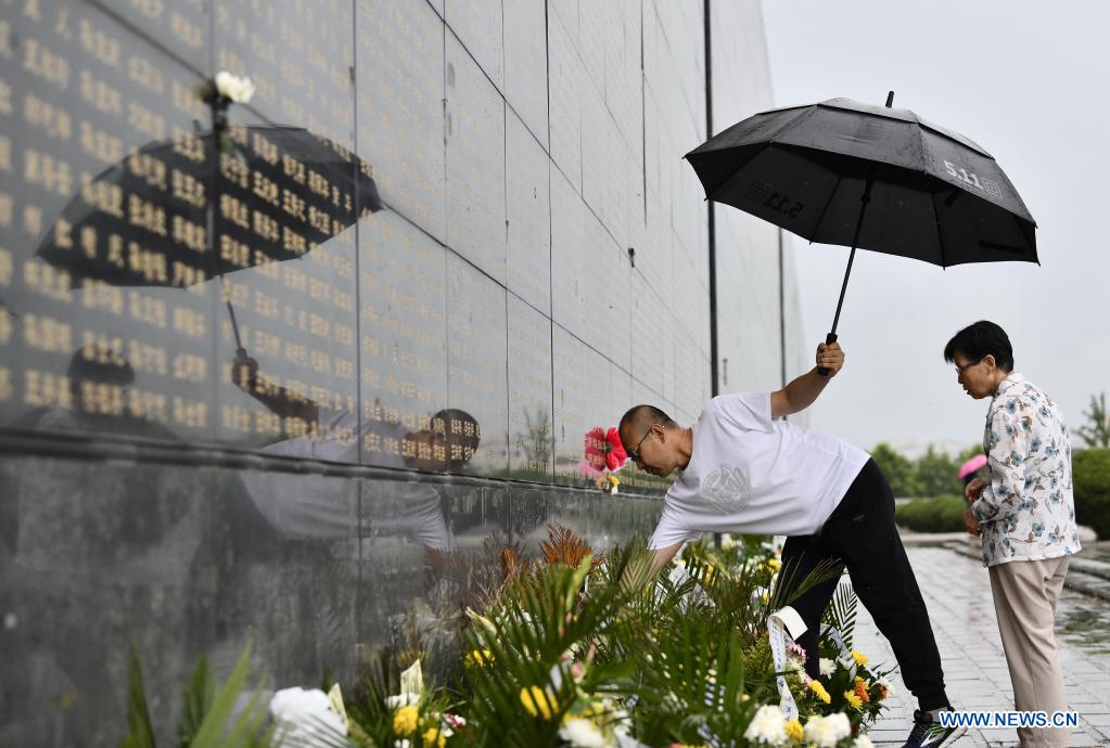 A resident presents flowers in front of a memorial wall at the Tangshan Earthquake Memorial Park in Tangshan, north China's Hebei Province, July 27, 2021. Wednesday marks the 45th anniversary of the Tangshan earthquake. The 7.8-magnitude quake struck the city of Tangshan in Hebei Province on July 28, 1976, killing more than 240,000 people and destroying virtually all buildings. (Xinhua/Mu Yu)