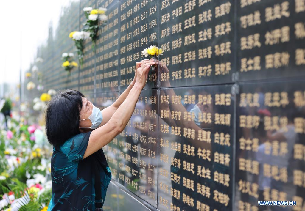 A woman presents flowers in front of a memorial wall at the Tangshan Earthquake Memorial Park in Tangshan, north China's Hebei Province, July 28, 2021. Wednesday marks the 45th anniversary of the Tangshan earthquake. The 7.8-magnitude quake struck the city of Tangshan in Hebei Province on July 28, 1976, killing more than 240,000 people and destroying virtually all buildings. (Xinhua/Jin Haoyuan)