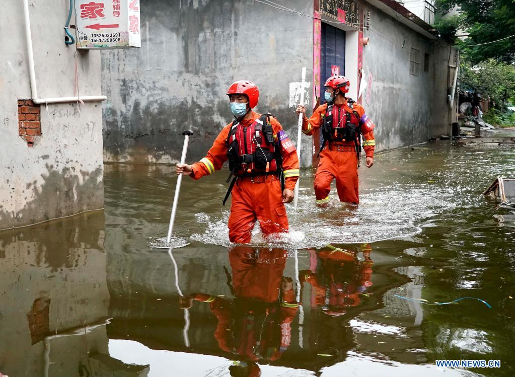 Rescuers search for stranded people while wading through waterlogged area in Weihui City, central China's Henan Province, July 28, 2021. Weihui City suffered from severe urban waterlogging due to the extremely heavy rainfall. Rescue and drainage work is still in progress there. (Xinhua/Li An)