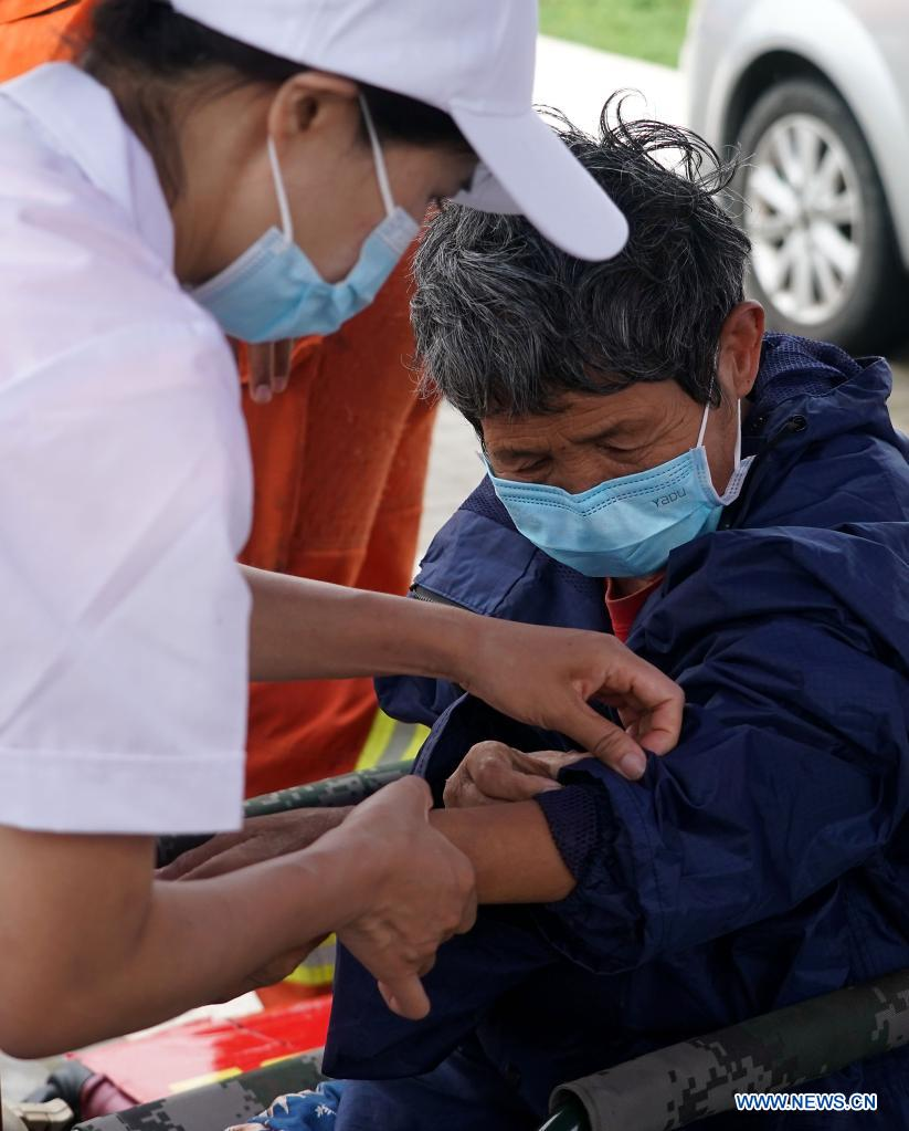 An elderly receives health check after being transfered to a safe area in flood-hit Weihui City, central China's Henan Province, July 28, 2021. Weihui City suffered from severe urban waterlogging due to the extremely heavy rainfall. Rescue and drainage work is still in progress there. (Xinhua/Li An)