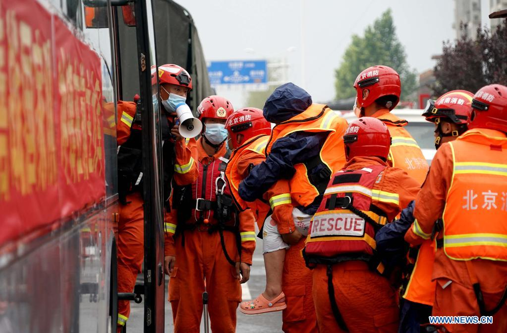 Rescuers transfer stranded people into a bus in Weihui City, central China's Henan Province, July 28, 2021. Weihui City suffered from severe urban waterlogging due to the extremely heavy rainfall. Rescue and drainage work is still in progress there. (Xinhua/Li An)