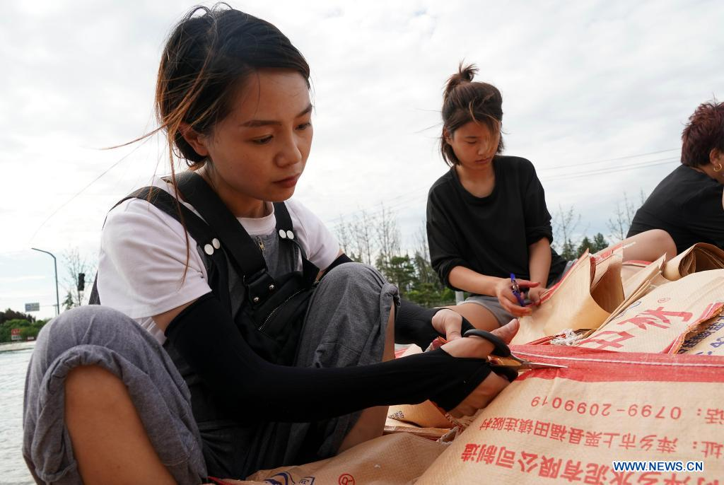 Rescuers, residents reinforce embankment in Xunxian, Henan
