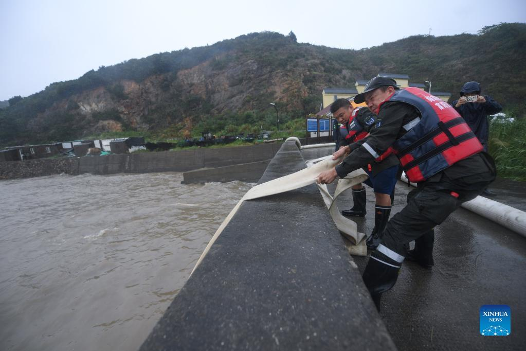 Rescuers pump rainwater out of a pool in Zhoushan, east China's Zhejiang Province, Sept. 13, 2021. Zhejiang Province has upgraded its emergency response to Typhoon Chanthu to the highest level, closing schools as well as suspending air and rail services in several cities. (Xinhua/Xu Yu)