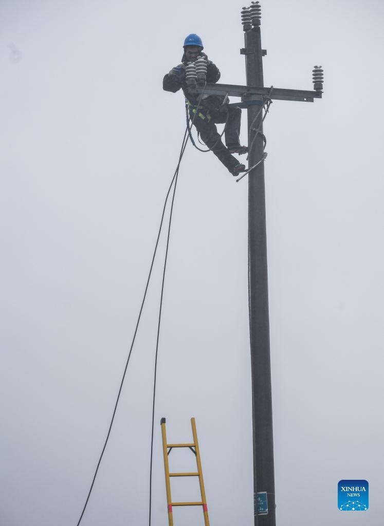A staff member of power supply company removes a length of broken wire due to the strong wind in Zhoushan, east China's Zhejiang Province, Sept. 13, 2021. Zhejiang Province has upgraded its emergency response to Typhoon Chanthu to the highest level, closing schools as well as suspending air and rail services in several cities. (Xinhua/Xu Yu)