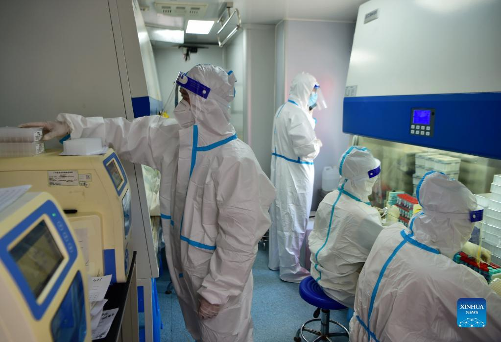 Staff members deal with nucleic acid testing samples in a PCR (polymerase chain reaction) lab in Xianyou County, southeast China's Fujian Province, Sept. 14, 2021. Three PCR labs have been built in the county to boost nucleic acid detection capacity. (Xinhua/Wei Peiquan)