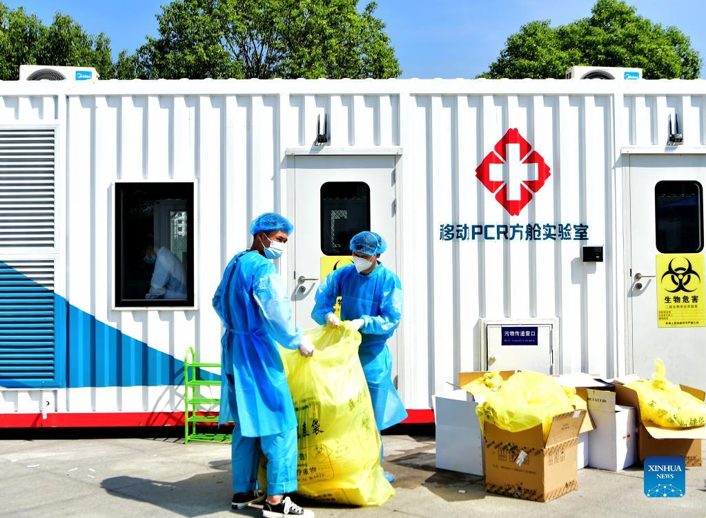 Staff members dispose medical waste outside a PCR (polymerase chain reaction) lab for nucleic acid testing in Xianyou County, southeast China's Fujian Province, Sept. 14, 2021. Three PCR labs have been built in the county to boost nucleic acid detection capacity. (Xinhua/Wei Peiquan)