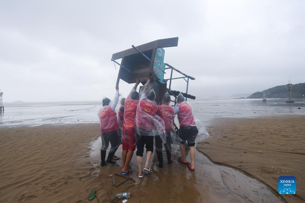 Volunteers lift up a lookout device at the Nansha beach resort in Zhoushan, east China's Zhejiang Province, Sept. 14, 2021. The disaster relief work is underway in Zhoushan as the influence of Typhoon Chanthu weakens. (Xinhua/Xu Yu)