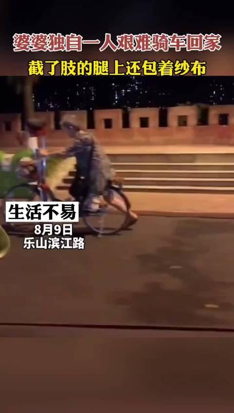 路上一位婆婆独自一人艰难骑自行车回家……