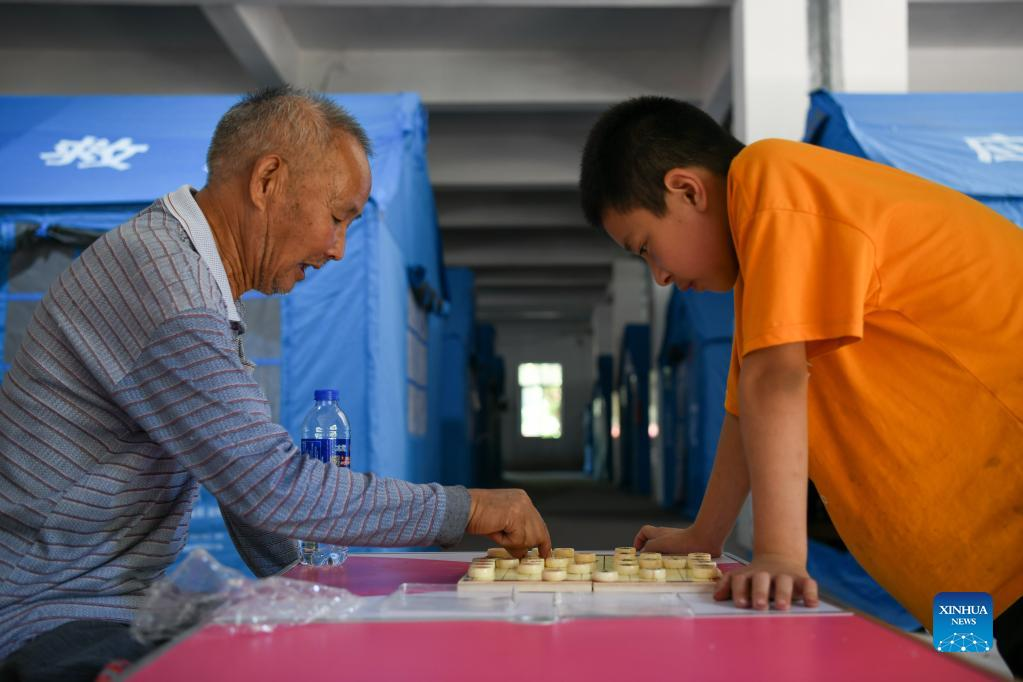 An elderly man plays Chinese chess with a child at a temporary resettlement site in Fuji Township of Luxian County, southwest China's Sichuan Province, Sept. 21, 2021. Residents from Sichuan Province who were affected by an earthquake that struck on Sept. 16 began returning home on Monday morning, as the local work priority has been shifted from emergency rescue to post-quake reconstruction. A 6.0-magnitude earthquake jolted Luxian County in the city of Luzhou at 4:33 a.m. on Sept. 16, leaving three people dead and 146 injured. (Xinhua/Xu Bingjie)