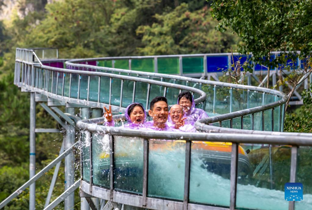 Tourists enjoy themselves on a glass-bottomed slide at the Great Nanjiang Canyon in Kaiyang County, southwest China's Guizhou Province, Oct. 2, 2021. Saturday was the second day of China's week-long National Day holiday. (Photo by Fan Hui/Xinhua)
